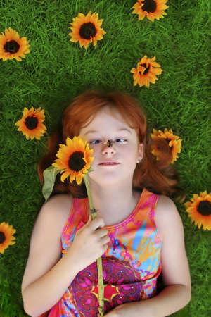 彼女の鼻に蜂とヒマワリで囲まれた緑の芝生の上に敷設小さな女の子 写真素材
