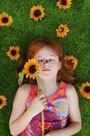 little girl laying on green grass surrounded by sunflowers with a bee on her nose Stockfoto