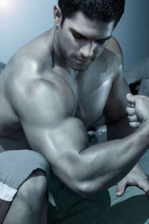 body work: body builder flexing his arm with blue treatment Stock Photo