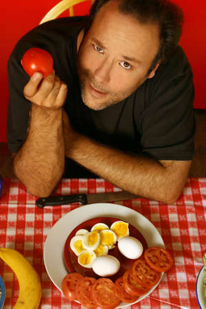 man holding a tomato while sitting at a table Stock Photo