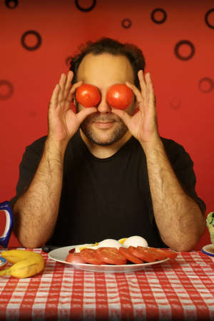 avant garde: bearded man sitting at a table holding two tomatoes on his eyes Stock Photo