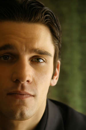 close up of a young mans face against green background