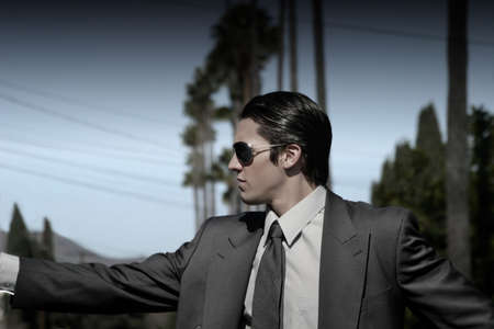 man in suit with sunglasses and palmtrees in the background