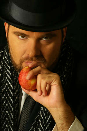 ambiguous: sinister bearded man holding an apple in front of his mouth