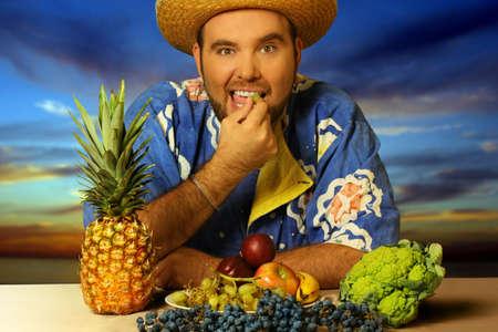 man eten: grote man het eten van fruit op het strand