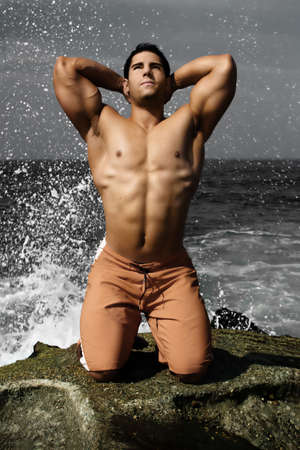 six packs: Bodybuilder on beach with ocean spray behind him