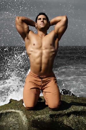 Bodybuilder on beach with ocean spray behind him