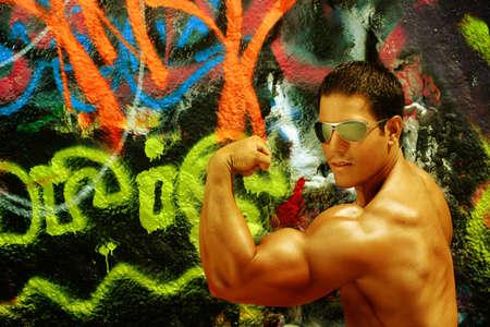 beach hunk: Bodybuilder flexing bicep against graffiti