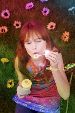Little red haired girl blowing bubbles with a rainbow effect photo