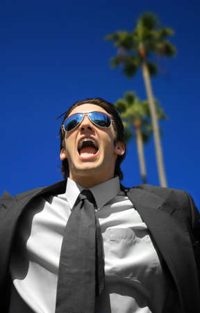 achievment: Young business man yelling against a blue sky