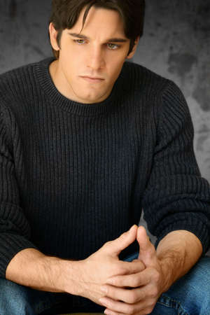 serious guy: Portrait of young man with hands clasped looking off