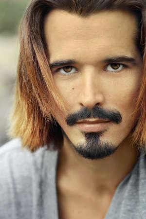 긴 머리와 콧수염을 가진 매력적인 남자