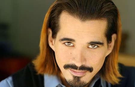 bigote: Retrato de hombre joven con perilla y pelo largo sonriente