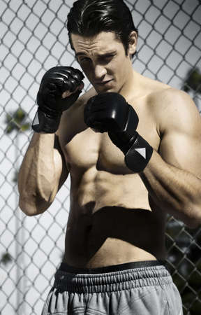 Young man with boxing gloves and gray sweatpants against fence Stock Photo - 3754634