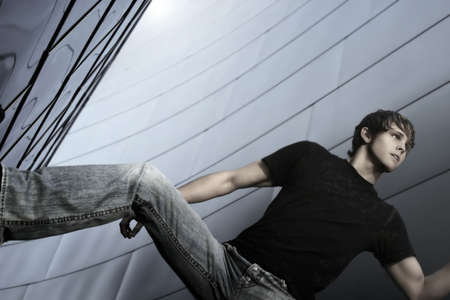 poses de modelos: Modelo masculino en jeans againstfuturistic metal de fondo Foto de archivo