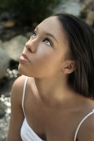 innocent: Beautiful young model looking up toward sky Stock Photo