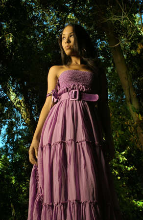 evening gown: Dramatic fashion shot of female model in purple flowing dress