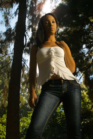 Full body portrait of beautiful African American young woman standing in forest