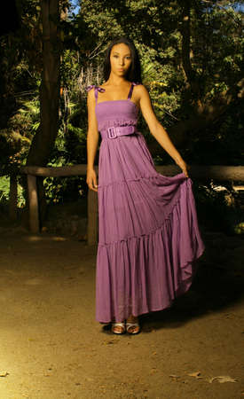 Dramatic fashion shot of female model wearing purple flowing dress