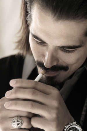 edgy: Male model with goatee and long hair lighting a cigarette Stock Photo