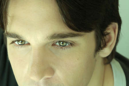 tight focus: Close-up portrait of male model showcasing green eyes with slight green cast.