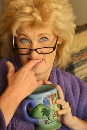 blonde mom: Funny portrait of older woman biting her fingerwith comic expression