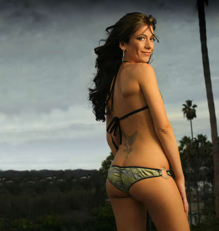 Beautiful female model in bikini with tattoo against gray cloudy sky photo