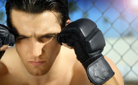 Horizontal close-up portrait of young man with boxing gloves photo