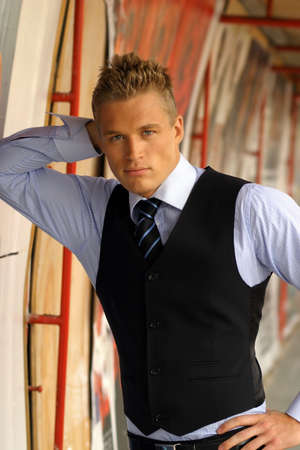 Portrait of young businessman leaning on a wall photo