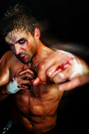 Gritty portrait of a sexy young, bloody boxer photo