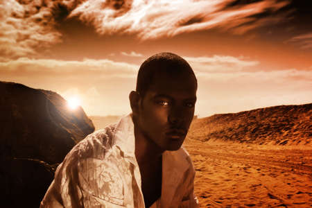 Portrait of good looking young African-American male against dunes with dramatic sky in red tones