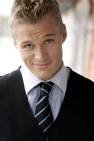 young male model: Close-up retrato de una sonriente joven conf�a en modelo masculino en la corbata y chaleco Foto de archivo