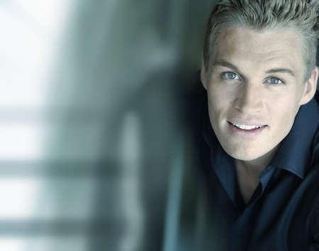 young male model: Horizontal cerca de retrato de un sonriente conf�a en los j�venes de sexo masculino con un modelo moderno futurista de fondo, con una gran cantidad de espacio de copia