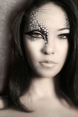 Close-up portrait of an enigmatic beautiful young girl with extreme fashion make up photo
