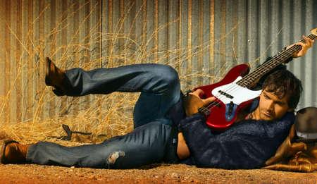 水平全身エレキギターを弾き毛皮でホット若い男の肖像 写真素材