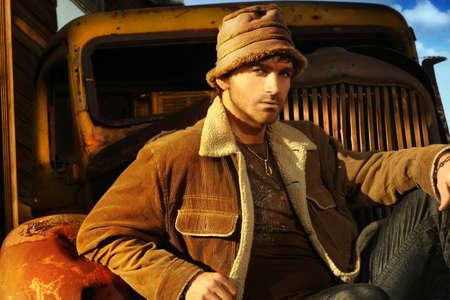 young male model: Horizontal retrato de una bonita joven modelo masculino en contra de un marr�n oxidado viejo cami�n Foto de archivo