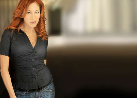 Full body portrait of a sexy red-headed woman in casual attire with lots of copy space