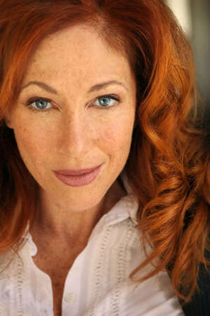 freckles: Close-up portrait of an attractive red haired woman with freckles Stock Photo