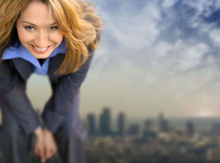 Young business woman smiling with city and clouds far in the distance behind her photo