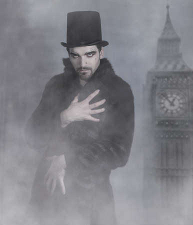Mysterious good looking man in fur coat and top hat surrounded by fog photo