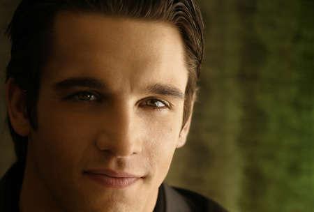 young male model: Horizontal cerca de retrato de una sonriente joven conf�a en modelo masculino