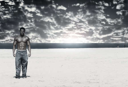 Hot shirtless bodybuilder walking on the beach with dramatic cloudscape and overall blue tinting.