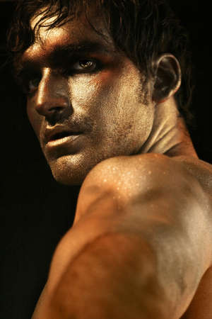 Dramatic portrait of intense looking shirtless male model in bronze and gold makeup turning