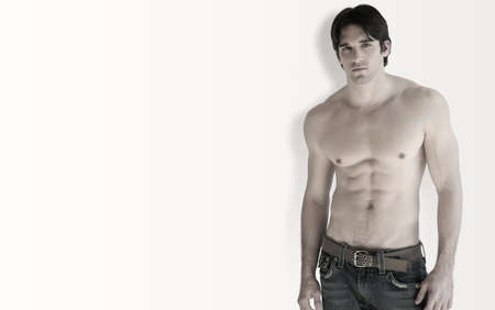 Full body portrait of young shirtless muscular man against white background with slight shadow and lots of copy space
