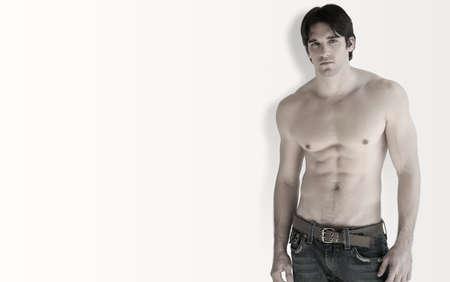 torso nudo: Per tutto il corpo ritratto di giovani shirtless muscolare contro l'uomo bianco con leggera ombra e un sacco di spazio copia