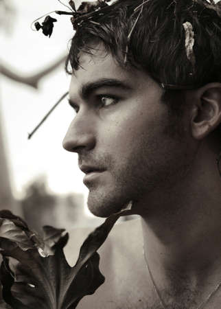 sensitivity: Close-up profile portrait of noble young man portraying Caesar with leaves and branches in his hair Stock Photo