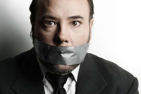 discreto: Dramática estilizada de cerca de un gran hombre de negocios con cinta adhesiva para cubrir su boca