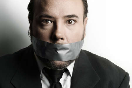 Dramatic stylized close-up of a very businessman with duct tape covering his mouth Stock Photo