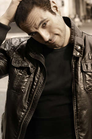 Portrait of a good looking man in classic leather jacket with hand on head