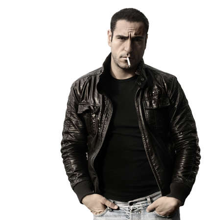 Portrait of a rebel type guy in classic leather jacket with cigarette in mouth against white background
